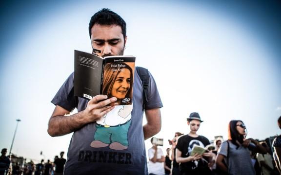 A man reads a book by Turkish writer Tezer Özlü, Eski Bahçe - Eski Sevgi (Old Garden - Old Love in English) in Taksim Square, Istanbul.