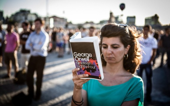 A woman reads George Orwell's dystopian novel Nineteen Eighty-Four in Taksim Square, Istanbul. IMAGE CREDIT: GEORGE HENTON.